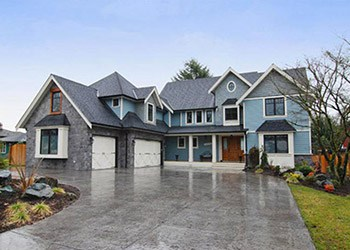 well-landscaped house property with double garage and large driveway on rainy day